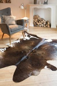 Rinderfell Fell Teppich braun beige Sessel Kamin Raumbild Reinkemeier