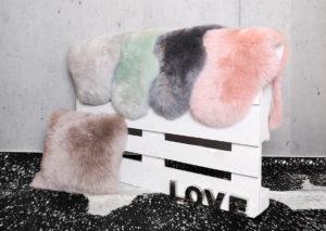Schaffell Rinderfell Fell Teppich grau gruen tuerkis anthrazit rosa schwarz beige palette Betonwand Reinkemeier